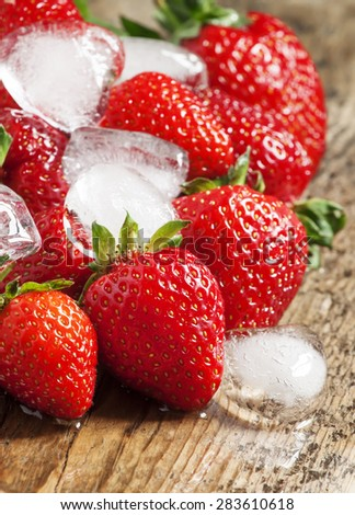 Fresh strawberries with ice on a wooden table, selective focus