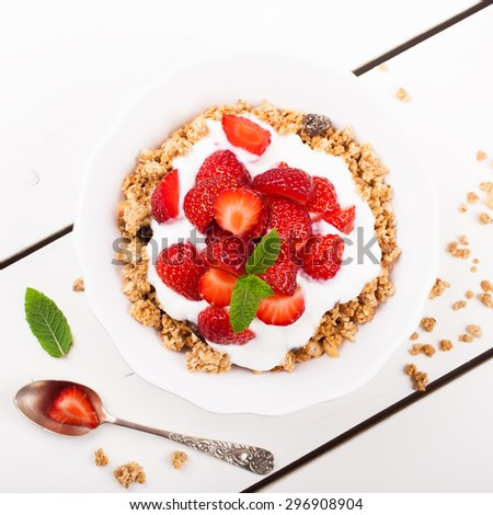 Fresh strawberries , yogurt and homemade granola for healthy breakfast on white background, selective focus. Top view. - stock photo