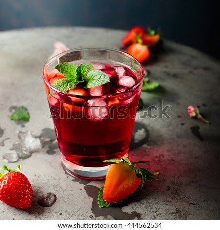 Fresh strawberry and mint drink/cocktail on grey background. Dark contrast style photo, closeup. Copy space for text - stock photo