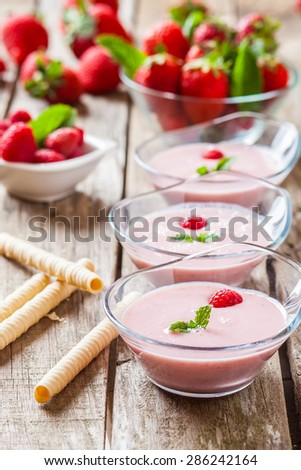 fresh strawberry and raspberry milkshake with mint leaves on glass - stock photo