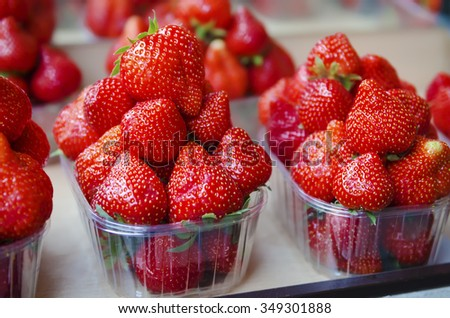 Fresh strawberry at market in plastic boxes, local food healthy background - stock photo