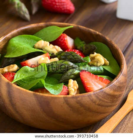 Fresh strawberry, green asparagus, baby spinach and walnut salad served in wooden bowl, photographed on dark wood with natural light (Selective Focus, Focus on the asparagus head in the middle)