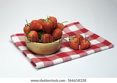 Fresh strawberry in a wooden bowl on Checkered tablecloth  isolated on white  background