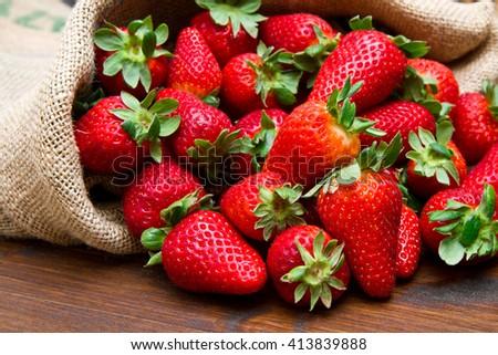 fresh strawberry in burlap sack on wood - stock photo