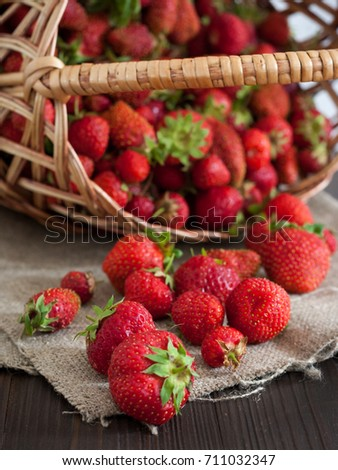Fresh strawberry in wicker basket. Rustic photo. Brown wooden background.