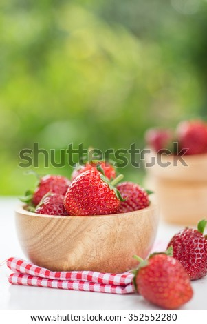 fresh strawberry in wooden bowl with nature background. - stock photo