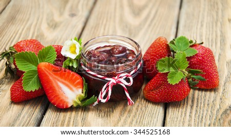Fresh strawberry jam in a jar of strawberries on a wooden background - stock photo