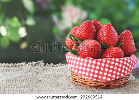 Fresh strawberry on sackcloth with green blur background - stock photo