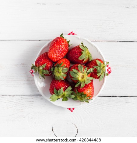 Fresh strawberry on the plate. Summer ripe strawberry top view, flat lay, square - stock photo