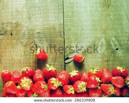 Fresh strawberry on weathering wooden background. Grunge style. - stock photo