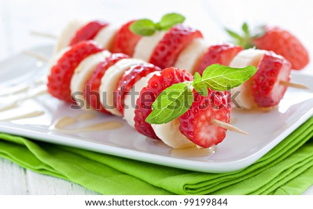 fresh strawberry skewers with banana and honey - stock photo