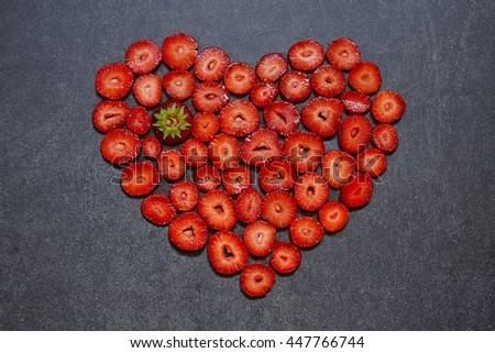 Fresh strawberry slice heart shape on black stone background - stock photo