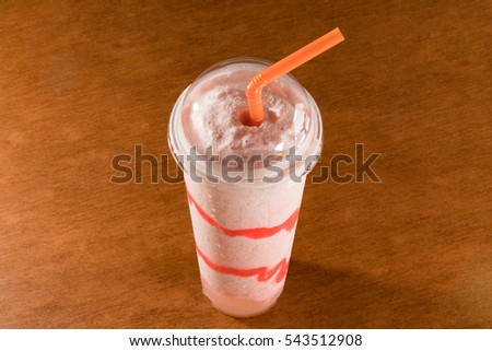 Fresh strawberry smoothie in plastic cup on ceramic floor tile
