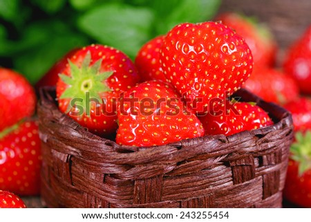 Fresh strawberry with mint leaves on a wooden surface