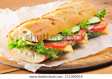 Fresh, submarine sandwich from baguette with ham, cheese, tomato, cucumber and lettuce - stock photo