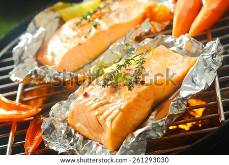 Fresh succulent marine salmon steaks flavored with sprigs of thyme grilling over a barbecue on aluminum foil with sweet pepper and baby carrots - stock photo