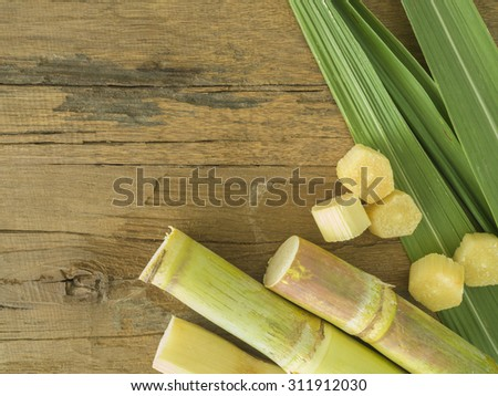 Fresh sugarcane cut into pieces on a wooden table with leaves and cane. - stock photo
