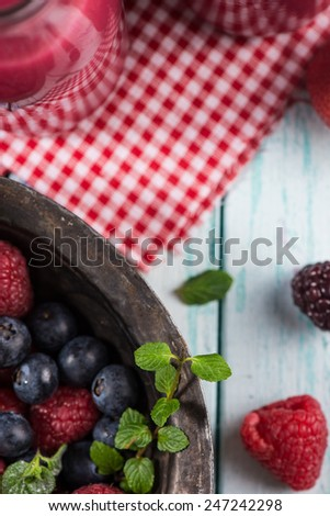 Fresh summer berries fruits in vintage bowl on rustic table - stock photo