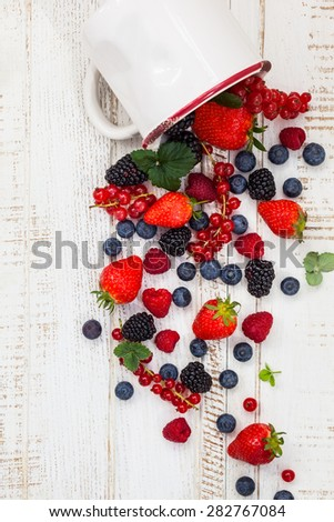 Fresh summer berries in vintage mug over wooden background,top view - stock photo
