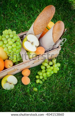 Fresh Summer Food Fruits Basket Picnic Apples Peaches Orange Grapes Bread Baguette with Sesame Green Grass - stock photo