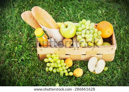 Fresh Summer Food in Picnic Basket on Green Grass. Horizontal image - stock photo