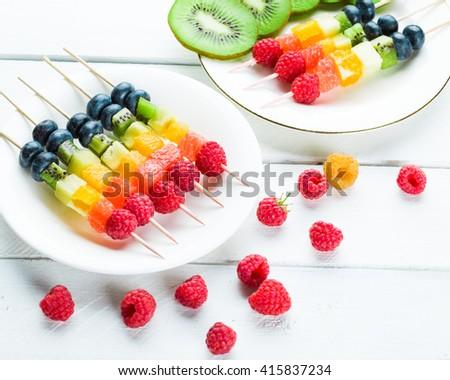 Fresh summer fruits on sticks. Studio shot - stock photo