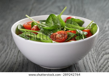 fresh summer organic salad with tomatoes cucumbers and spinach on wooden table - stock photo