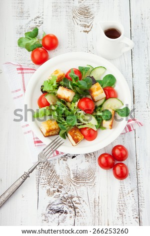 Fresh summer salad with cherry tomatoes, spinach and roasted tofu cheese in a plate on white wooden background, top view - stock photo