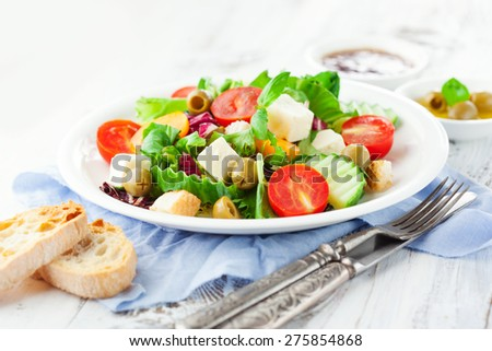 Fresh summer salad with cherry tomatoes, spinach, arugula, romaine and lettuces in a plate on white wooden background, selective focus - stock photo