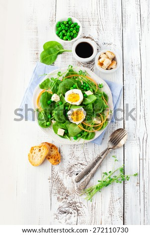 Fresh summer salad with green beans, spinach leaves and eggs on white wooden background, top view - stock photo