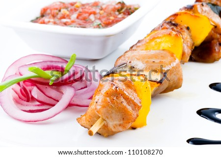 Fresh summer shish kebab on a dish on a white background with sauce and an onions - stock photo