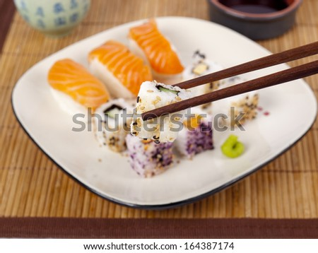 Fresh sushi and sashimi on a plate with a cup of sake and chopsticks - stock photo