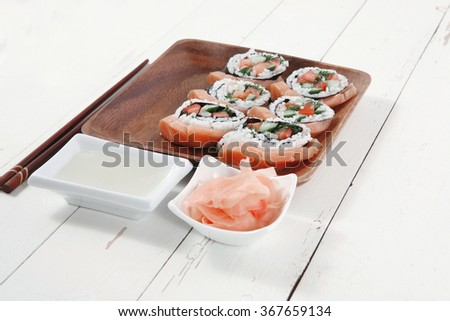 fresh sushi sashimi nigiri with raw salmon slice red ginger and japanese vinegar on wooden plate over white table - stock photo