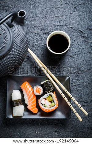 Fresh sushi served in a black ceramic - stock photo