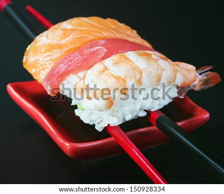 fresh sushi served in a red plate with black stripes. Focus on the first sushi with salmon. - stock photo