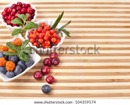 Fresh sweet berries in a wooden striped surface board texture background - stock photo