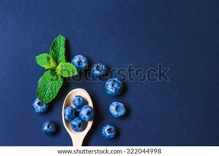 Fresh sweet blueberry fruit and leaf of mint.. Dessert healthy food. Group of ripe blue juicy organic berries. Raw summer diet. Delicious nature vegetarian ingredient. Black background. - stock photo