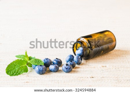 Fresh sweet blueberry fruit and leaf of mint in medical bottle from pills. Dessert healthy food. Group of ripe blue jui?y organic berries. Raw summer diet. Delicious nature vegetarian ingredient - stock photo