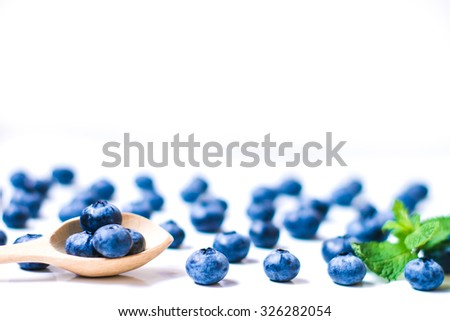 Fresh sweet blueberry fruit and leaf of mint in wooden spoon. Dessert healthy food. Group of ripe blue juicy organic berries. Raw summer diet. Delicious  vegetarian ingredient. Shallow depth of field - stock photo