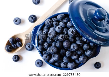 Fresh sweet blueberry fruit in bowl with wooden spoon. Dessert healthy food. Group of ripe blue juicy organic berries. Raw summer diet. Delicious nature vegetarian ingredient.