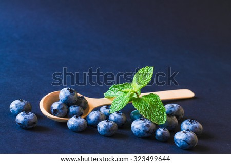 Fresh sweet blueberry fruit in hte wooden spoon with leaf of mint. Dessert healthy food. Group of ripe blue juisy organic berries. Raw summer diet. Delicious nature vegetarian ingredient. - stock photo