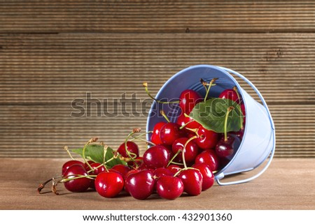 Fresh sweet cherries on the table boards - stock photo