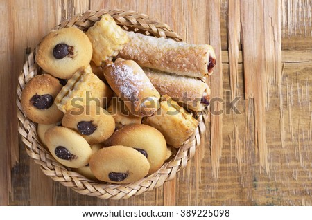 Fresh sweet cookies in a wicker bowl on old wooden table, top view - stock photo