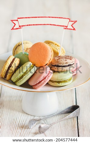 Fresh sweet macarons on a cake stand with empty decorative name tag. Toned photo. Vintage style.