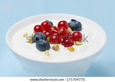 fresh sweet yogurt with berries and pistachios, close-up, horizontal - stock photo