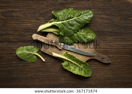 Fresh swiss chard leaves on a wooden background. - stock photo