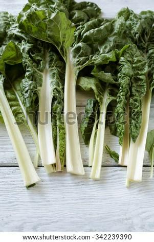 fresh swiss chard on white boards, vegetables  - stock photo
