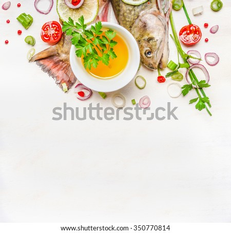 Fresh tail and head of fish with oil and seasoning for cooking on white wooden background, top view. Healthy food or diet nutrition concept. - stock photo