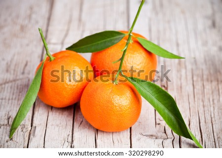 fresh tangerines with leaves on rustic wooden table