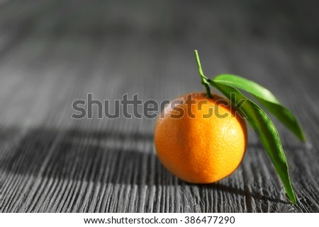 Fresh tangerines with leaves on wooden table, closeup - stock photo
